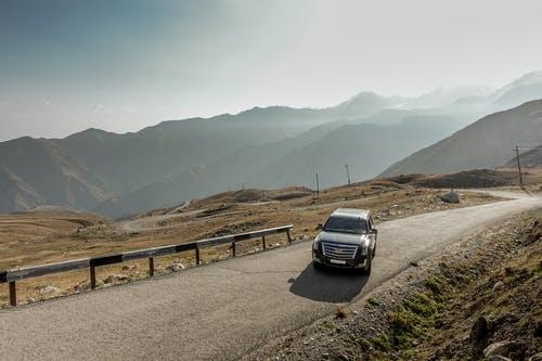 Black Escalade on the mountain road